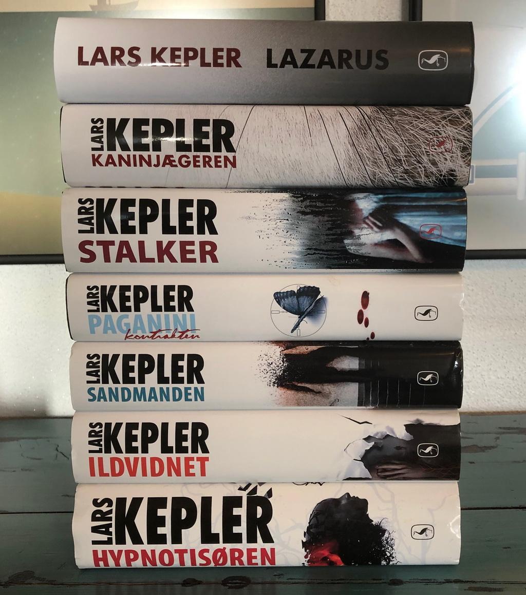 Lazarus af Lars Kepler er øverst i stakken med de øvrige bøger i serien.